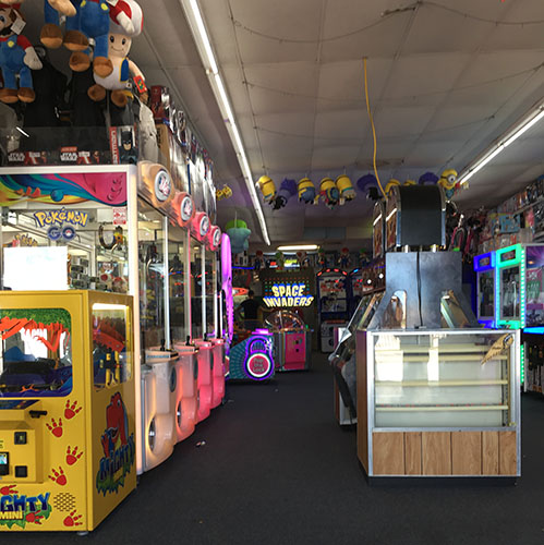 An arcade with many prize catcher games.